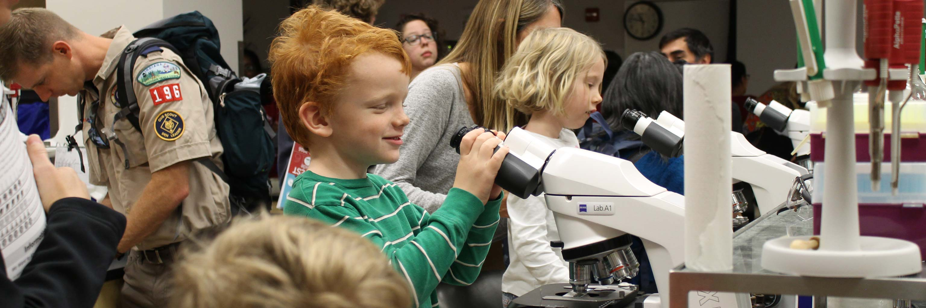 children and students interact during a science event