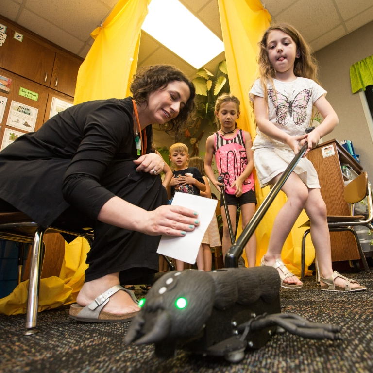 IU researcher Kylie Peppler helps students at Clear Creek Elementary use BioSim wearable technology. A young female student pushes the ant toy.