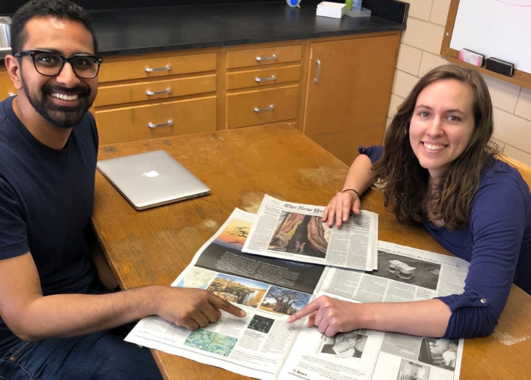 Courtney Ellison (right) and Ankur Dalia point to the article about their research printed in The New York Times on June 19, 2018.