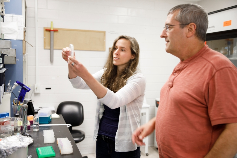 IU Ph.D. student Courtney Ellison (left) examines a sample in the lab with Yves Brun, IU Distinguished Professor of Biology. 2018.