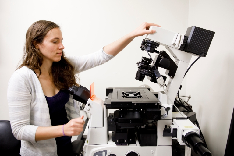Courtney Ellison adjusts a fluorescence microscope in Jordan Hall.