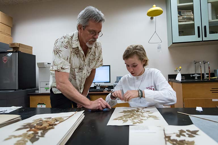 Director Eric Knox instructs Maggie Vincent on how to affix a label to a pressed plant specimen sheet.