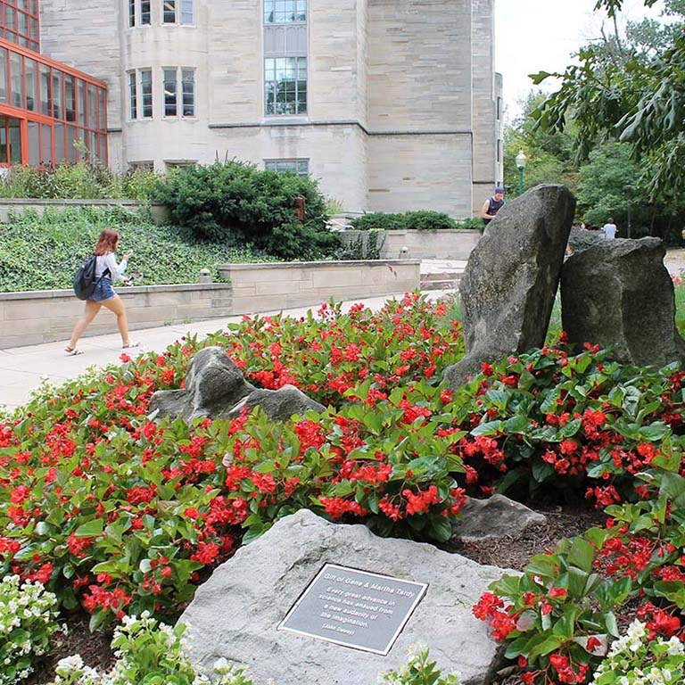 A student walks by Jordan Hall. Red begonias bloom in a flowerbed in the foreground.