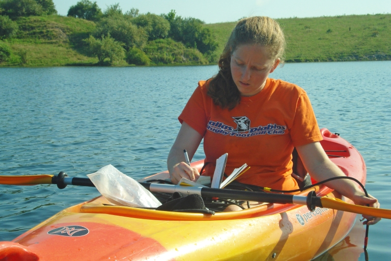 Marta Shocket making research notes while sitting in kayak on lake.