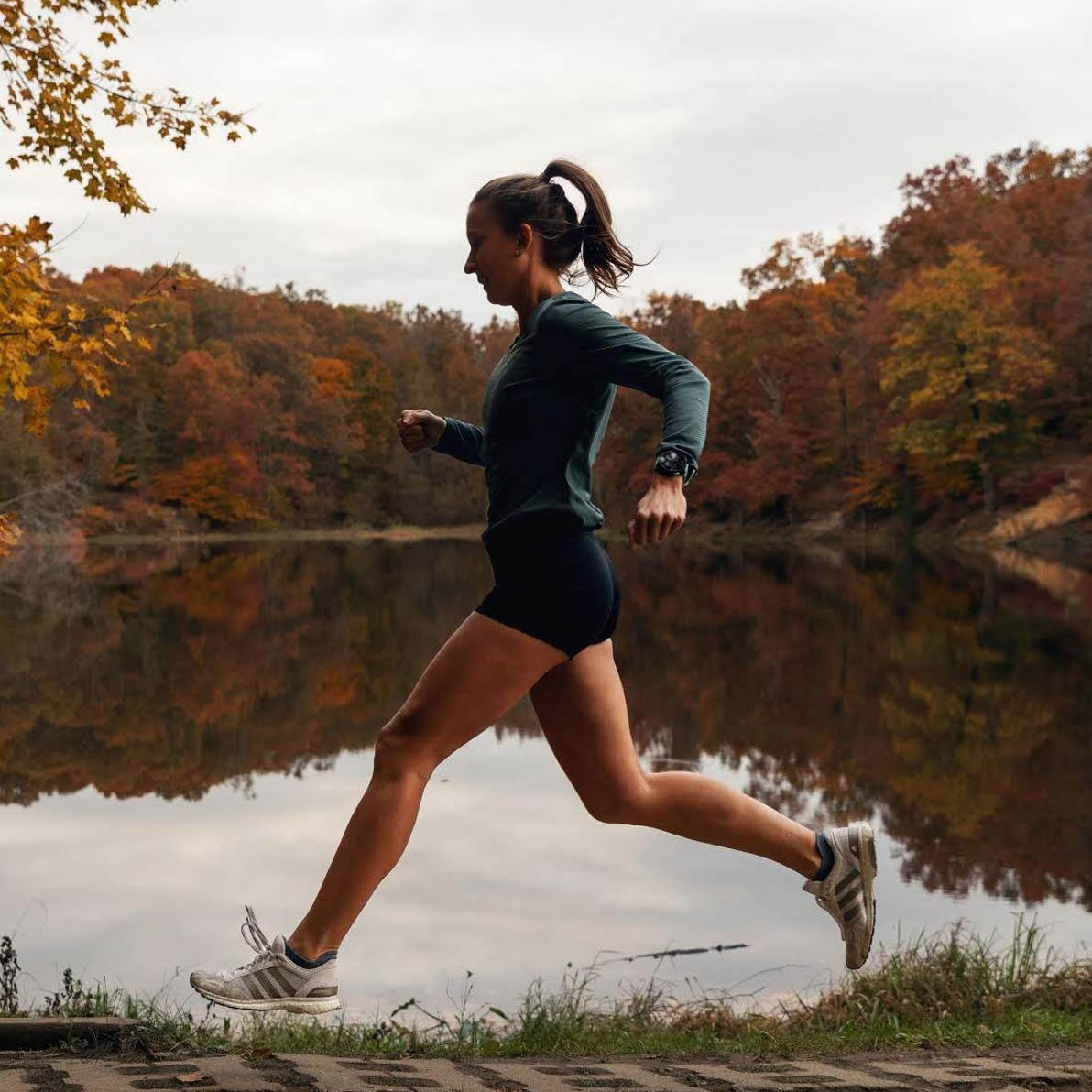 Olivia Ballew runs past a lake as she trains for a marathon. Beautiful fall foliage in the background.