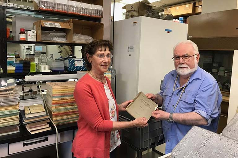 IU Distinguished Professor of Biology Thom Kaufman hands off collection of historically significant Drosophila research documents to Elise Calvi of the Lilly Library.