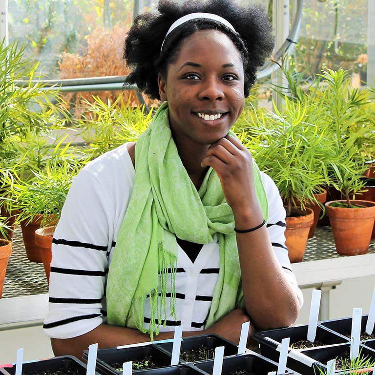 Lekeah Durden poses with her research plants in the Jordan Hall greenhouse.