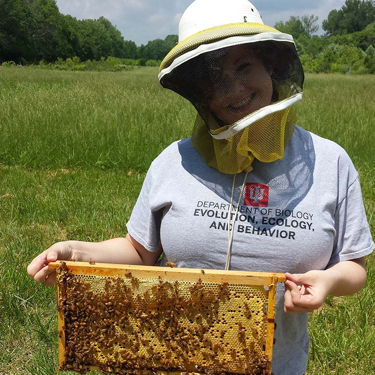 Delaney Miller, wearing a beekeeper's hat with netting, presents a frame from a bee hive with honeycomb and lots of bees.