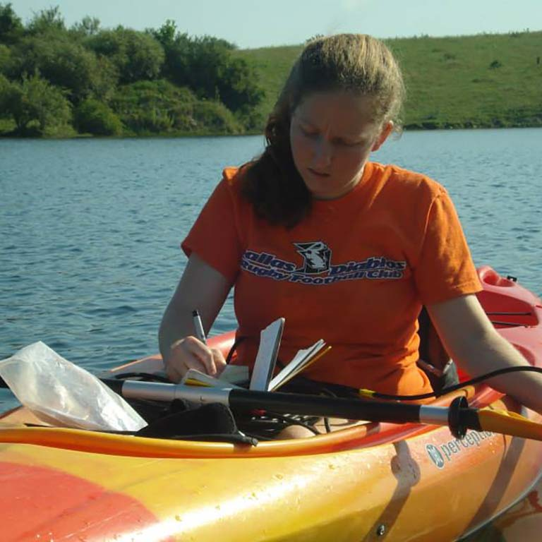 Marta Shocket in a kayak writes in her notebook while collecting samples from a lake in Greene-Sullivan State Forest in southern Indiana.