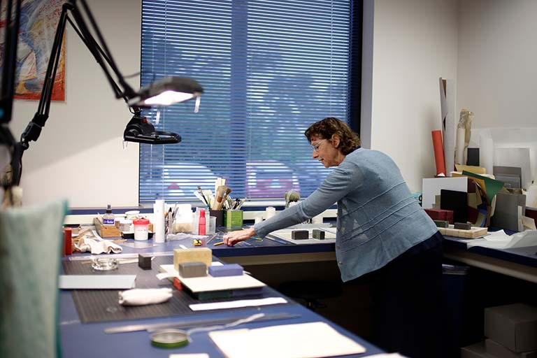Elise Calvi works with the collection of historically significant Drosophila research documents in the Lilly Library preservation room.