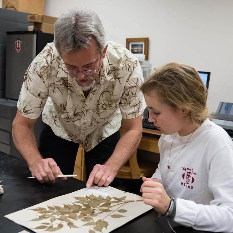Director Eric Knox (left) instructs undergraduate student Maggie Vincent on how to affix a label to a specimen sheet.