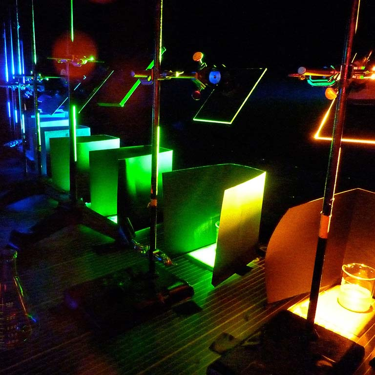 Mirrors are used to reflect different colors of light onto beakers with samples of the ocean bacterium Synechococcus under an experiment overseen by researchers from IU.