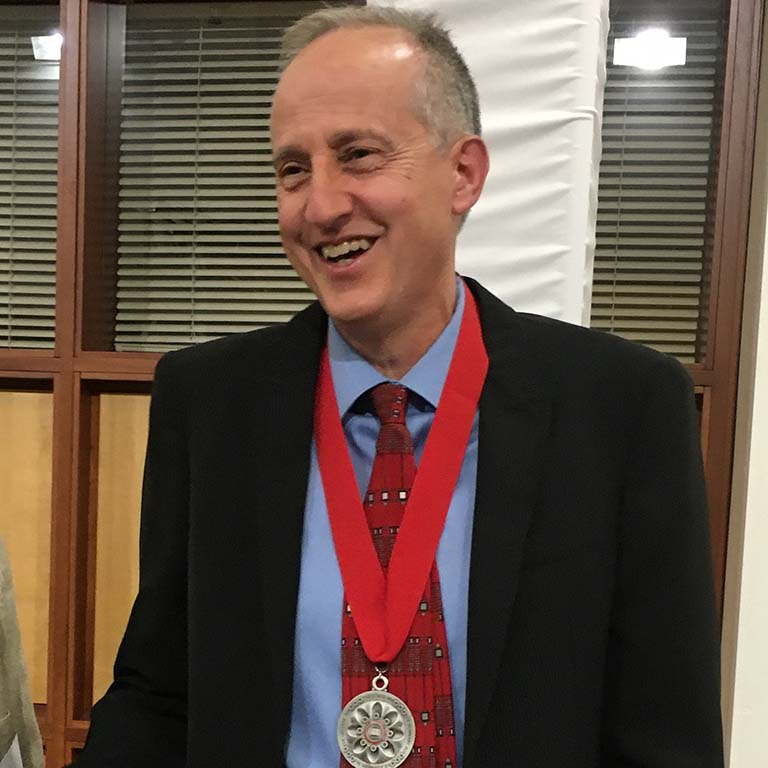 Jeff Palmer smiles as he wears the silver medal on a red ribbon around his neck after being awarded the IU President's Medal for Excellence.