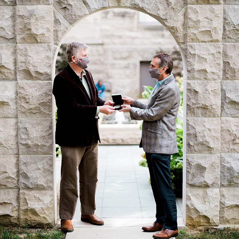 Rick Van Kooten presents Craig Pikaard (left) with the IU Bicentennial Medal. Both are standing outdoors in a stone archway on the IU Bloomington campus.