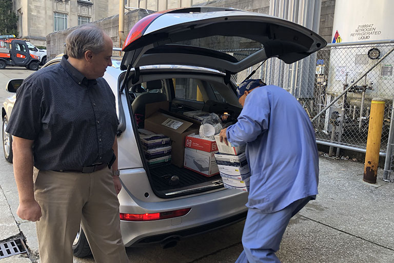 Health care workers loading donated personal protective equipment into vehicle.