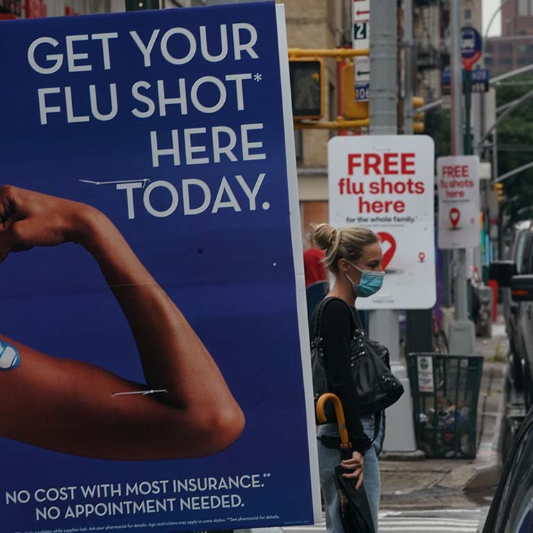 Signs encouraging people to get their flu shot are displayed on light posts along a street as a woman wearing a face mask waits to cross the traffic.