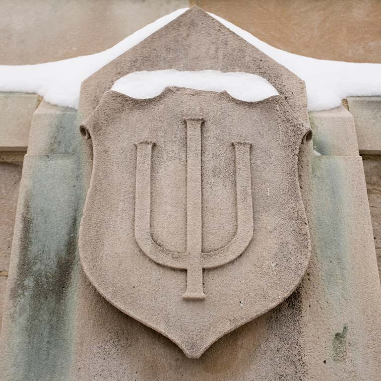 IU trident carved in limestone extends from an outside wall. Snow rests on the top of the engraving.