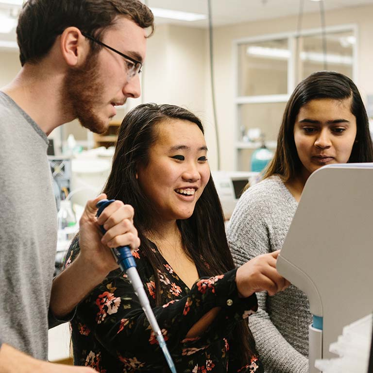 Three students working in a research lab.