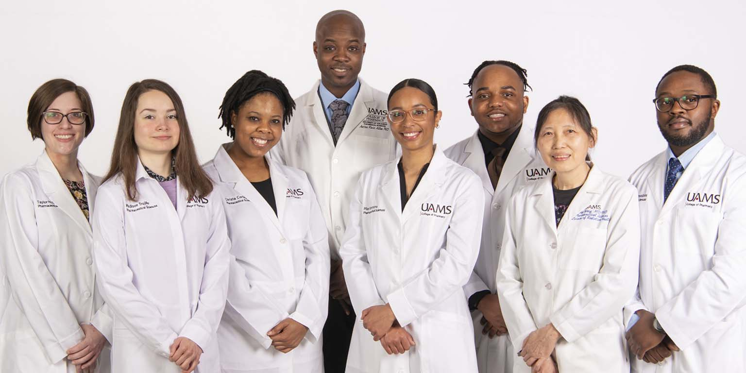 Antiño R. Allen poses with members of his lab.  All are dressed in their white research coats.