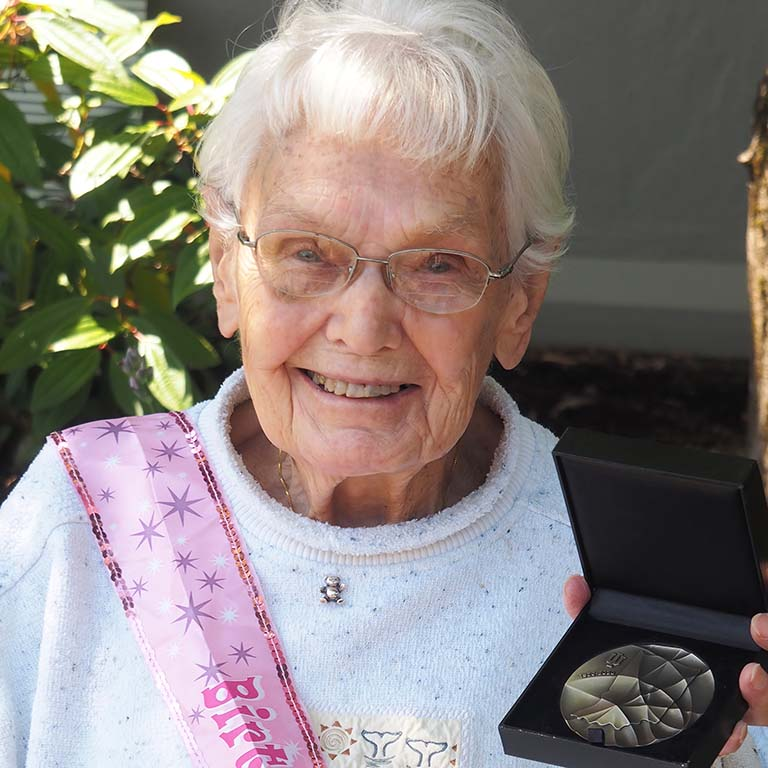 Alumna and retired IU Biology faculty member Ruth Dippell smiles as she holds up the IU Bicentennial Medal