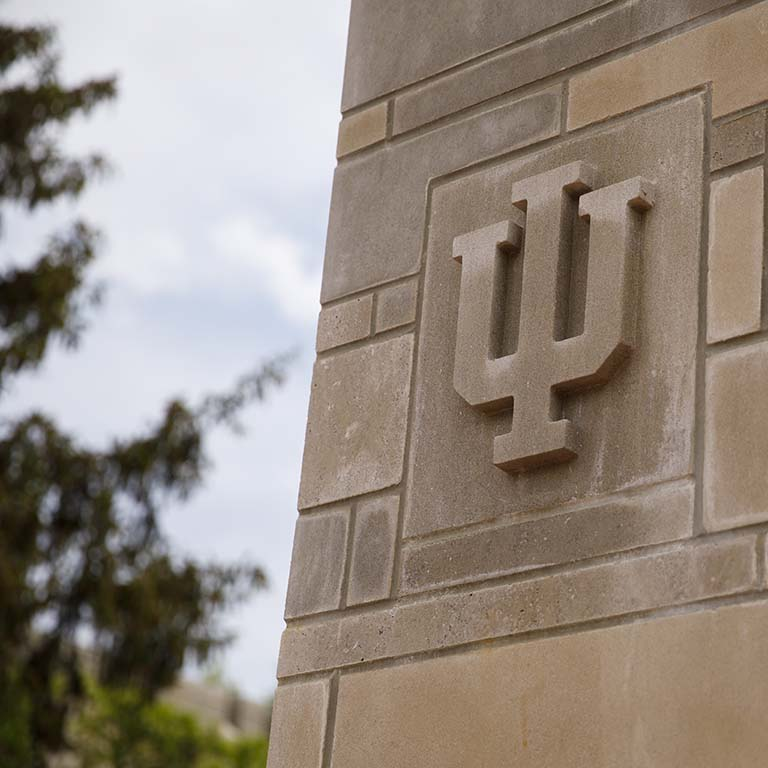 The IU trident carved in limestone is displayed in a stone-block pillar.