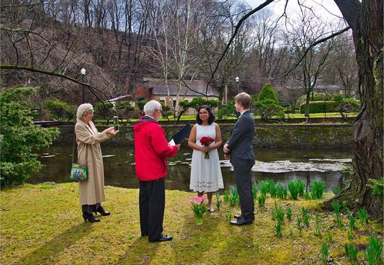 Amrita Bhattacharya and Jon Zarling stand in a lovely outdoor setting with pond and greening shrubs and grass as the daffodil foliage pushes through the ground on March 20, 2020, in Pennsylvania during their civil wedding ceremony.