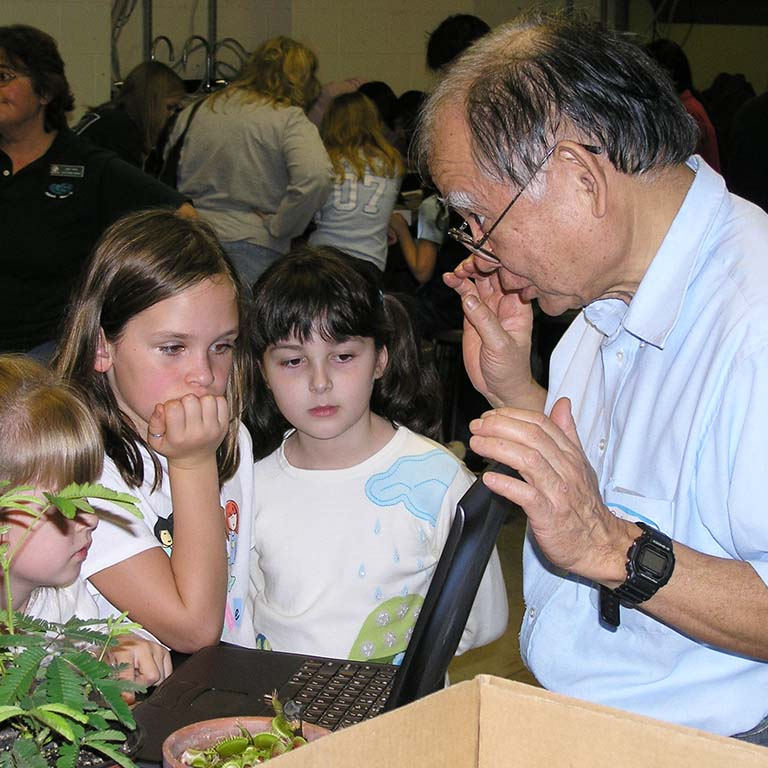 Bob Togasaki talks with Girl Scout Brownies at a 2004 outreach program.