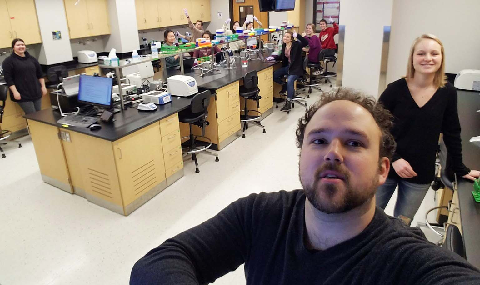 Instructor Mike Manzella takes a selfie of himself and his lab full of students.